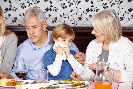wipe: Child cleaning mouth with napkin at family dinner