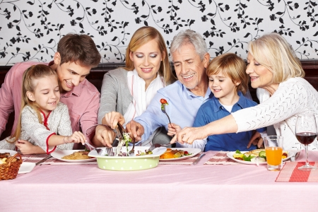 Hungry family reaching for food at dinner table at the same time photo