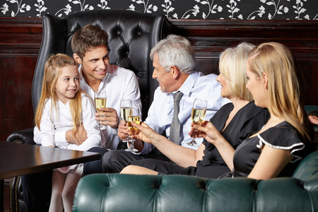 Happy family at wedding reception drinking glass of sparkling wine photo