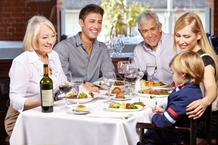 grandparents: Happy family eating together in a restaurant with child and grandparents