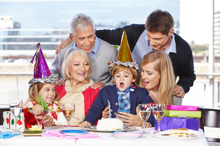 blowing out: Happy boy blowing out a candle at his birthday party Stock Photo