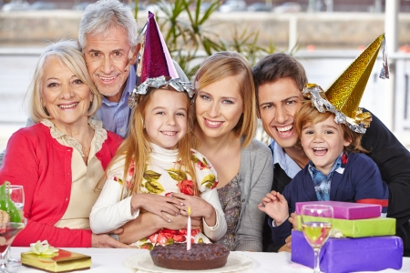 childs birthday party: Happy family celebrating childs birthday party together with grandparents Stock Photo