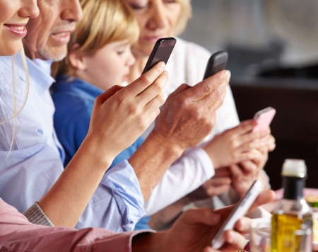 multiple family: Many people checking their smartphones at the dinner table Stock Photo