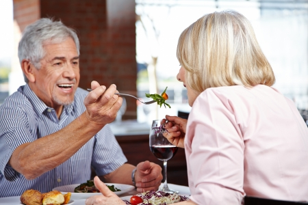 letting: Man in restaurant letting his woman taste from his food