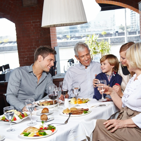 Happy family with two children and grandparents eating in a restaurant photo