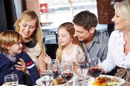 dadã  daughter: Familia que come el almuerzo con sus hijos y la abuela Foto de archivo