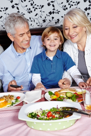 a little dinner: Happy little child eating with his grandparents at the dinner table