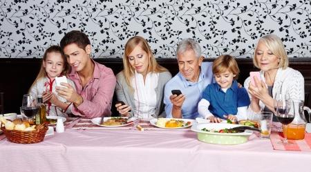 Famille regardant leurs smartphones à la table du dîner Banque d'images