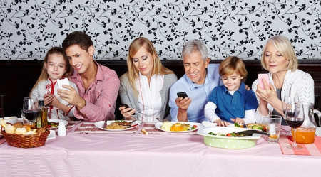 Family looking at their smartphones at the dinner table photo