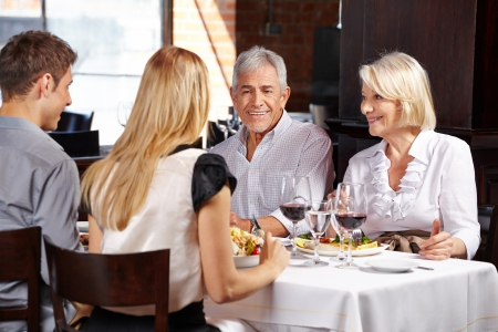 Couple with family eating out in a restaurant and talking photo