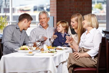 семья: Счастливая семья с ребенком вместе улыбается в ресторане