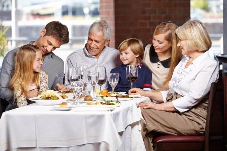 mujeres felices: Familia feliz con los ni�os y las personas mayores comer en un restaurante Foto de archivo