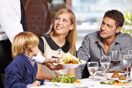 Waiter serving a family in a restaurant and bringing a full plate photo