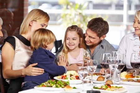 familia comiendo: Dos niños jugando juntos en un restaurante durante la visita de la familia Foto de archivo