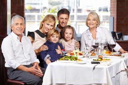familia cenando: Retrato de una familia feliz con ni�os y abuelos en la mesa del comedor Foto de archivo