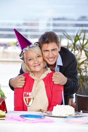 Happy adult man celebrating birthday with his senior mother photo
