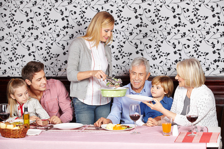 Mother serving healthy food to family at the dinner table Stock Photo - 23051901