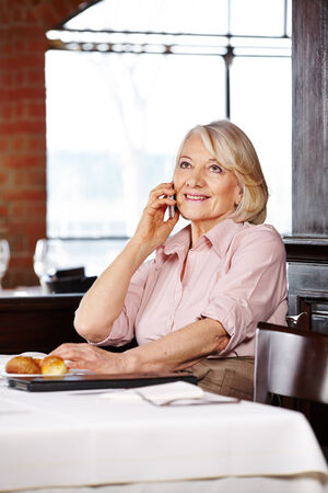 Senior woman using her smartphone to make a call in a restaurant photo