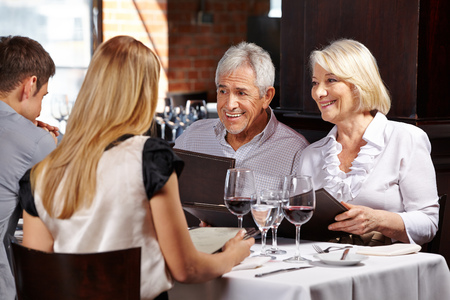 Smiling senior couple with family in a restaurant holding a menu photo