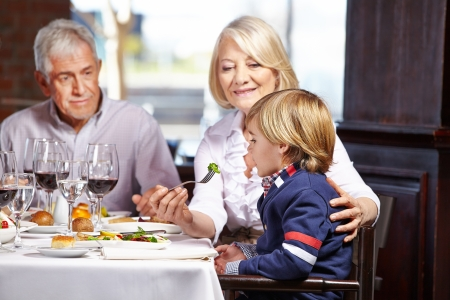 Child eating out with his grandparents in a restaurant Stock Photo