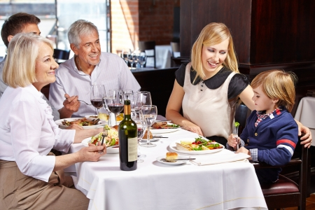 Family with child and grandparents eating out in a restaurant photo