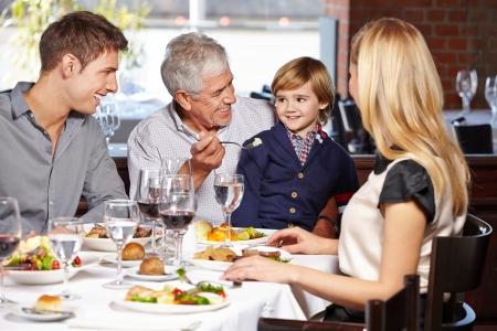 Happy grandfather feeding his grandson in a restaurant photo