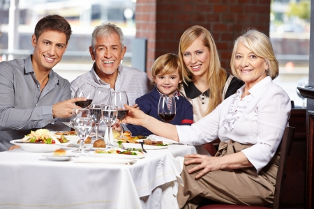 Happy family with child clinking glasses in a restaurant Stock Photo