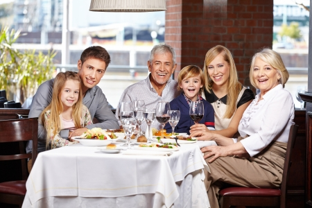 table of contents: Happy family with children and seniors eating out in a restaurant Stock Photo