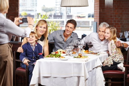 grandma: Grandmother taking family picture in restaurant with her smartphone Stock Photo