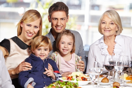 Happy family with children and grandmother sitting at lunch table photo