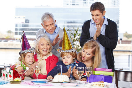 childrens birthday party: Happy birthday child blowing out a candle with its family Stock Photo