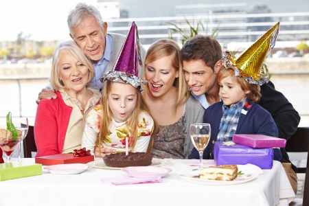 blow out: Happy girl blowing out candles at birthday party with her family Stock Photo