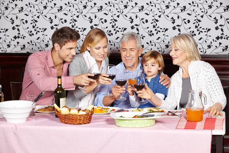 table of contents: Happy family at dinner table clinking glasses of red wine Stock Photo