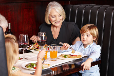 Smiling grandparents eating out with their grandchildren in a restaurant photo