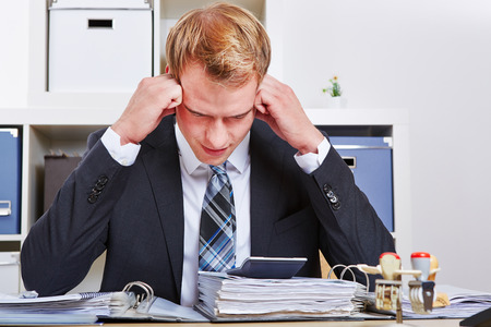 Manager sitting with burnout syndrome in his office and starring at files photo