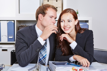 Business man telling woman a secret by whispering it into her hear photo
