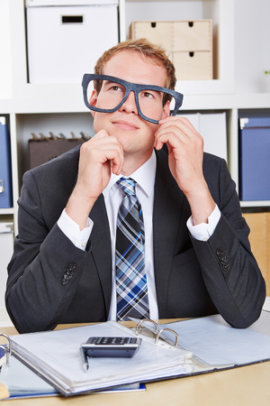 overachiever: Pensive business man with oversized nerd glasses in the office Stock Photo