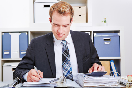 audit: Accountant doing financing in the office with a calculator for a tax audit Stock Photo