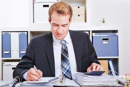 auditor�a: Contador operar con financiamiento en la oficina con una calculadora para una inspecci�n fiscal Foto de archivo