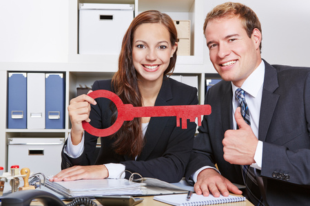 Two happy business people with a red key holding thumbs up in the office photo