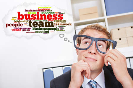 overachiever: Business man with tag cloud thinking about teamwork in the office Stock Photo