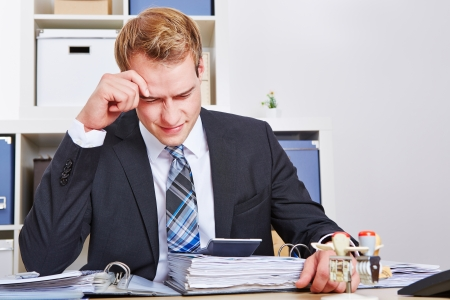 Stressed businessman sitting with burnout in his office photo