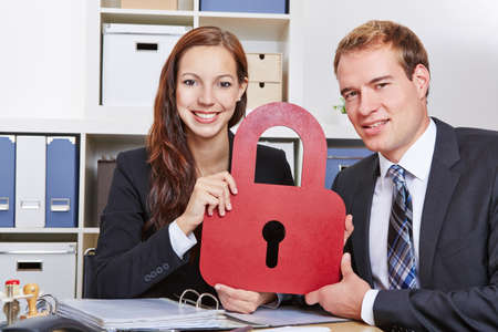 Data security in business office with two business people holding a lock photo