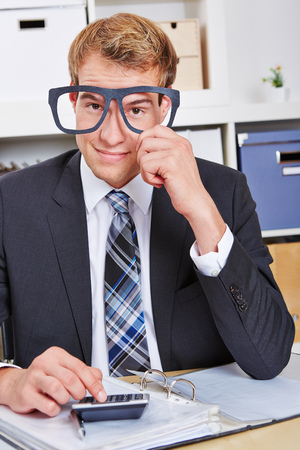 overachiever: Smiling business man holding nerd glasses in front of his face in the office