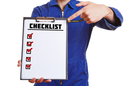 Construction worker holding clipboard with checklist and pointing with finger to it photo