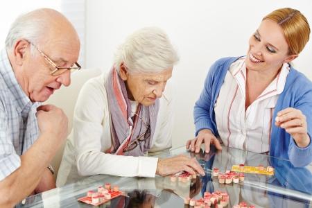 Senior paar spelen Bingo met ouderenzorg assistent in verpleeghuis