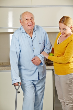 Senior man with crutches in the kitchen getting help from eldercare assistant photo