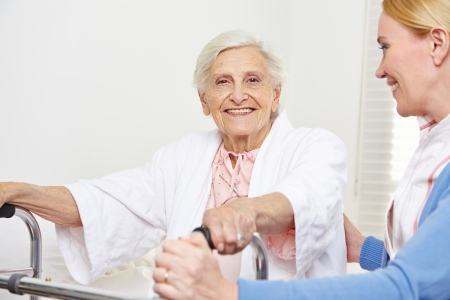 nursing staff: Happy senior woman sitting with geriatric nurse on her bed