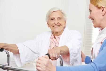 enfermeria: Mujer mayor feliz que se sienta con la enfermera geri�trica en su cama