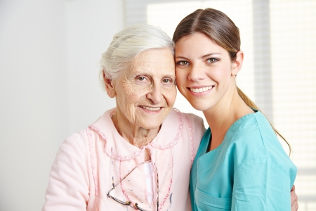 Smiling caregiver embracing happy senior woman in nursing home photo